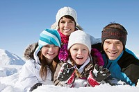 Parents and children lying in snow, smiling at camera