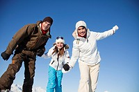 Couple and daughter in ski wear smiling at camera