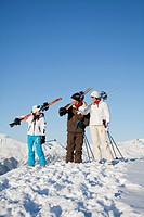Couple and daughter carrying skis