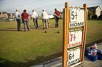 Men playing a game of lawn green bowls on a summer evening, Aberystwyth Wales UK