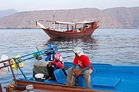 Two local fishermen watching the arrival of a dhow ship in the port of Khasab, Musandam, Sultanate of Oman
