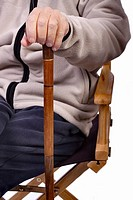 Mature man seated holding a walking stick