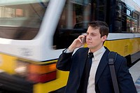 Businessman on cell phone outside in front of train