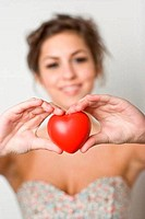 Teenage girl holding a heart shape object