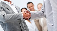 Two businessmen shaking hand in front of their colleagues in the office