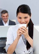 Smiling confident Businesswoman drinking a coffee at her desk in the office