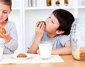 Smiling Siblings eating biscuits and drinking milk in the kitchen