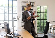 Businessman reading a magazine in an office