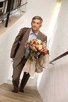 Man with a bouquet walking upstairs, elevated view