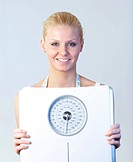 Friendly woman holding a scales and smiling at the camera with focus on woman