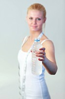 Young friendly woman holding a bottle of water with focus on water