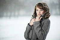 Young woman standing with coat in snow