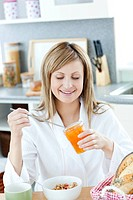 Cute woman having a breakfast in the kitchen at home