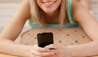 Close_up of a woman sending a text lying on the floor at home