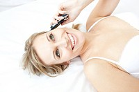 Laughing woman talking on phone lying on her bed at home