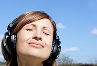 Relaxed woman listenng music with headphones outdoors