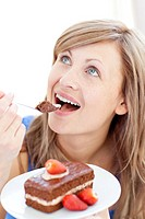 Delighted woman holding a piece of chocolate cake at home