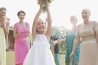 Girl catching bridal bouquet