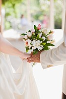 Close up of bride and groom holding bouquet