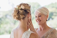 Mother touching bride's face