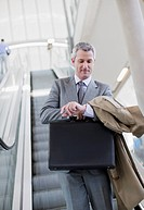 Businessman descending escalator and checking the time