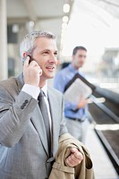 Businessman talking on cell phone on train platform