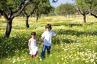 A boy and a girl holding hands in a yellow flower field