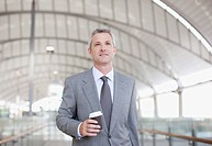 Businessman walking and holding coffee