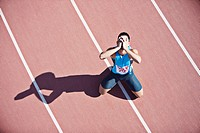 Disappointed runner kneeling on track