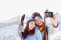 Couple with skis taking self_portrait