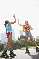 Women on rollerblades high fiving