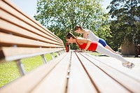 Friends doing push-ups on park bench (thumbnail)