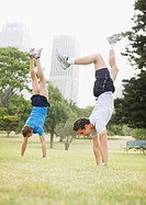 Couple doing handstands in urban park