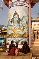 Indian people go about their daily business in front of a pillar painted with the Hindu god Shiva on that ghats of Varanasi, Uttar Pradesh, India, Asi...