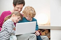 Close_up of a man assisting his son and daughter in using a laptop