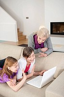 Two girls using a laptop on a couch with their grandmother standing beside them