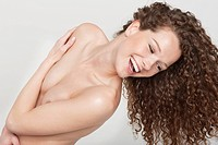 Woman covering her breasts and smiling