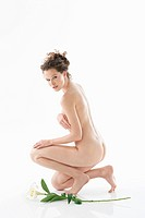 Naked woman kneeling beside a flower