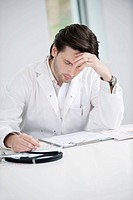 Male doctor examining a medical report and looking upset
