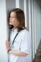 Female doctor looking out of a window