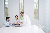 Three doctors examining a medical report