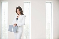 Businesswoman holding a file and checking the time