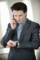 Businessman checking the time and talking on a mobile phone