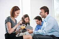 Woman eating food with their colleagues sitting with her