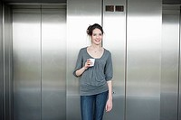 Businesswoman holding a disposable cup and smiling
