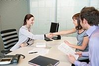 Female real estate agent shaking hands with a couple