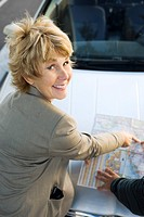 Woman checking road map, smiling at camera