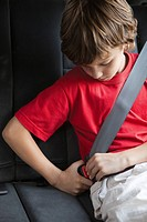 Boy fastening car seat belt