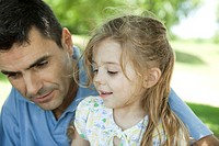 Father and young daughter talking outdoors