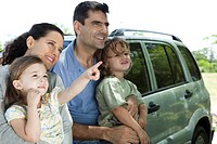 Family leaning against car, all looking as daughter points at something in distance (thumbnail)
